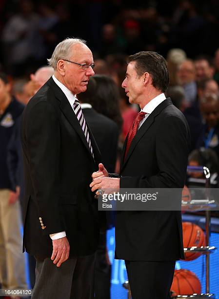 Head coach Jim Boeheim of the Syracuse Orange and head coach Rick Pitino of the Louisville Cardinals talk before coaching against each other during...