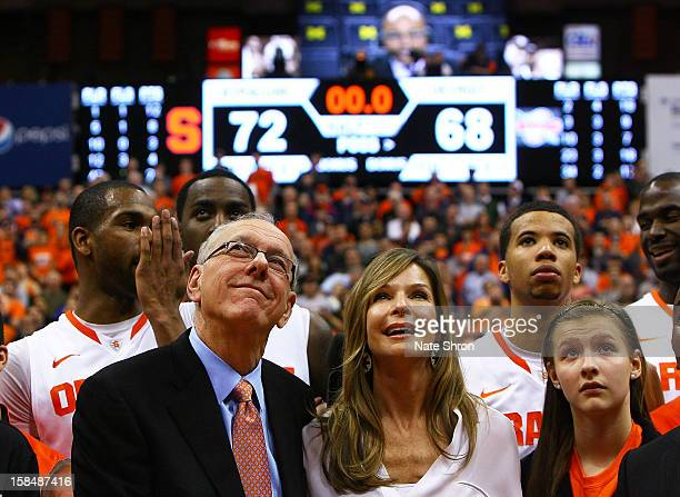 Head coach Jim Boeheim of the Syracuse Orange looks on to the video screens as he stands next to wife Juli Boeheim and daughter Jamie Boeheim to...