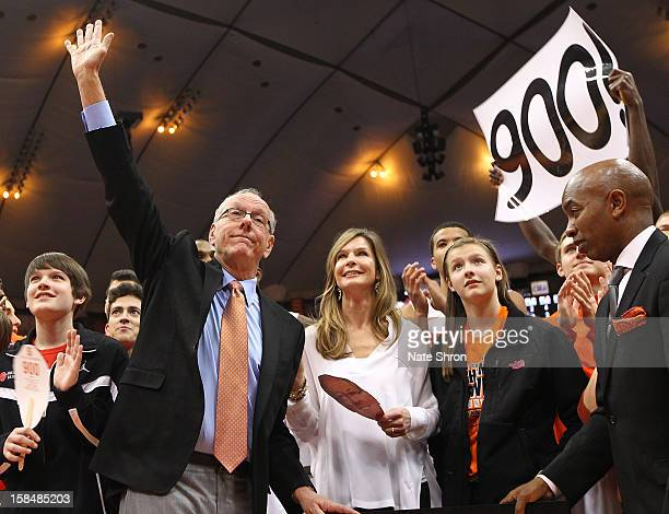 Head coach Jim Boeheim of the Syracuse Orange waives to the crowd as he stands next to wife Juli Boeheim during a presentation on the court after his...