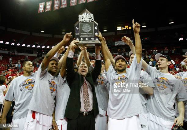 Head coach Jim Boylen of the Utah Utes and his players hoist the Mountain West Conference trophy after defeating the San Diego State Aztecs 52-50...