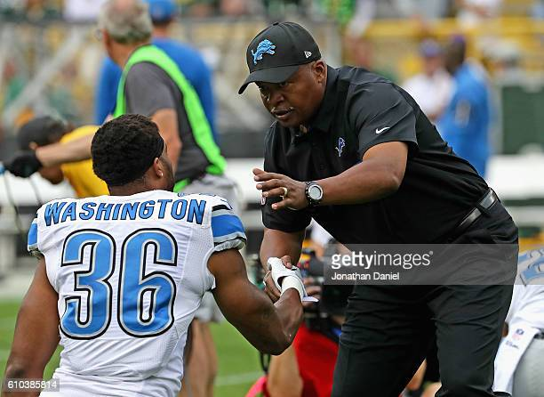 Head coach Jim Caldwell of the Detroit Lions shakes hands with Dwayne Washington during warm-ups before a game against the Green Bay Packers at...