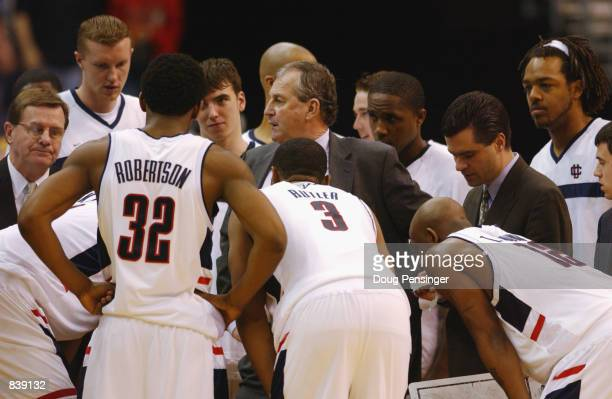 Head Coach Jim Calhoun of the University of Connecticut Huskies talks to his team in the huddle with assistant coaches Tom Moore and George Blaney in...