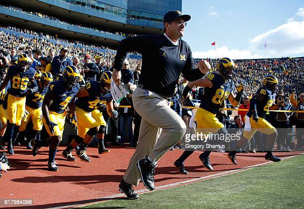 Head coach Jim Harbaugh leads the team onto the field while playing the Illinois Fighting Illini on October 22 2016 at Michigan Stadium in Ann Arbor...