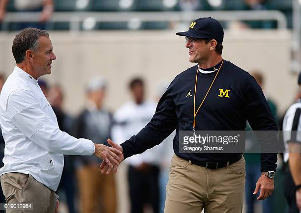 Head coach Jim Harbaugh Michigan Wolverines shakes hands with head coach Mark Dantonio of the Michigan State Spartans prior to the game at Spartan...