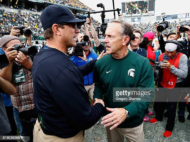 Head coach Jim Harbaugh Michigan Wolverines shakes hands with head coach Mark Dantonio of the Michigan State Spartans after a 3223 Michigan win at...