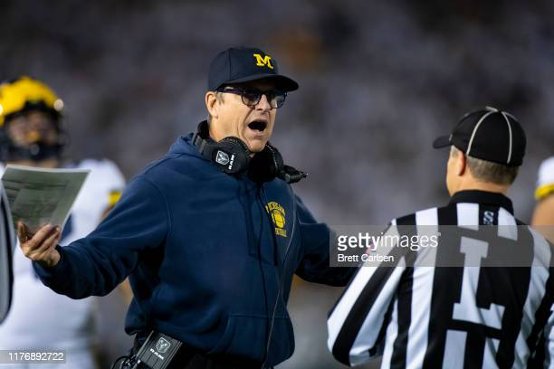 Head coach Jim Harbaugh of the Michigan Wolverines discusses a previous play with a line judge during the fourth quarter against the Penn State...