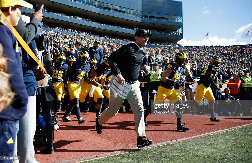 Head coach Jim Harbaugh of the Michigan Wolverines leads the team onto the field to play the Illinois Fighting Illini on October 22, 2016 at Michigan Stadium in Ann Arbor, Michigan.