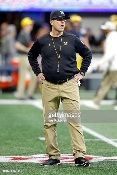 Head coach Jim Harbaugh of the Michigan Wolverines looks on during warm ups prior to the ChickfilA Peach Bowl against the Florida Gators at...