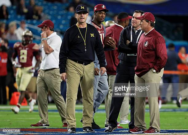 Head coach Jim Harbaugh of the Michigan Wolverines talks to head coach Jimbo Fisher of the Florida State Seminoles prior to their Capitol One Orange...