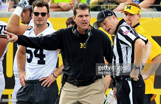 Head coach Jim Harbaugh of the Michigan Wolverines talks with an official during the first half of the Buffalo Wild Wings Citrus Bowl game against...