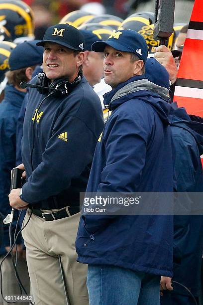 Head coach Jim Harbaugh of the Michigan Wolverines talks with his brother Baltimore Ravens head coach John Harbaugh on the sidelines during the first...