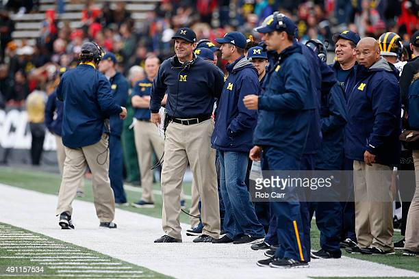 Head coach Jim Harbaugh of the Michigan Wolverines talks with his brother Baltimore Ravens head coach John Harbaugh on the sidelines during the...