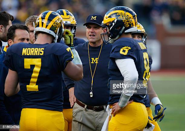 Head coach Jim Harbaugh of the Michigan Wolverines talks with Shane Morris and John O'Korn during the Michigan football spring game on April 1 2016...
