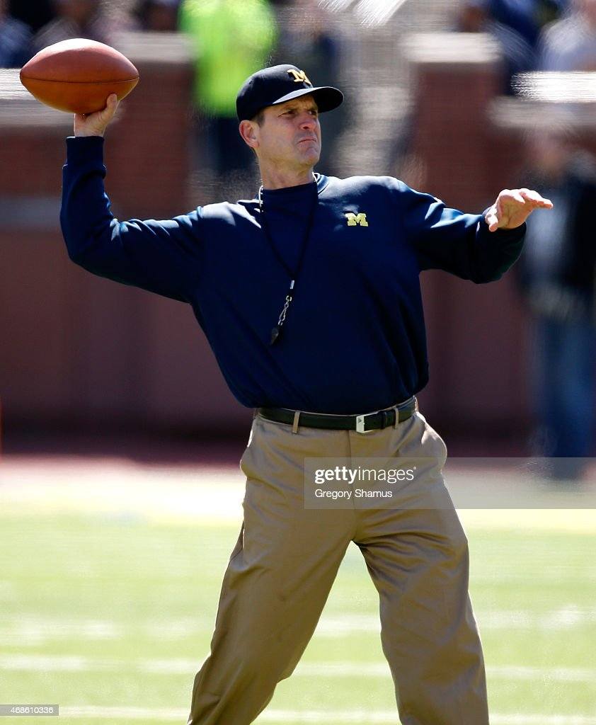 Head coach Jim Harbaugh of the Michigan Wolverines throws a football during the Michigan Football Spring Game on April 4, 2015 at Michigan Stadium in Ann Arbor, Michigan.