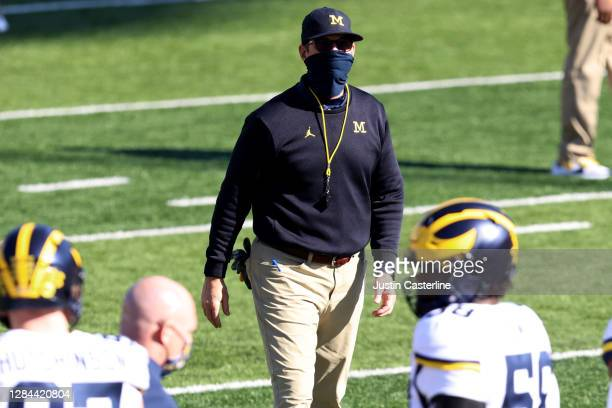 Head coach Jim Harbaugh of the Michigan Wolverines walks on the field during warm ups before the game against the Indiana Hoosiers at Memorial...