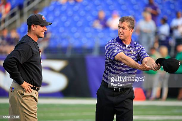 Head coach Jim Harbaugh of the San Francisco 49ers and his brother head coach John Harbaugh of the Baltimore Ravens talk before the start of their...