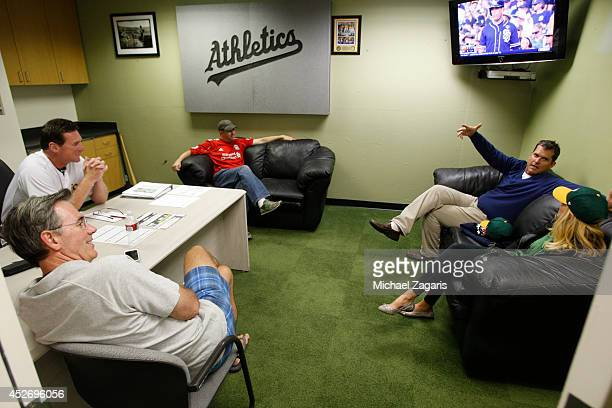 Head Coach Jim Harbaugh of the San Francisco 49ers and his wife Sarah visit with Manager Bob Melvin of the Oakland Athletics in his office with...