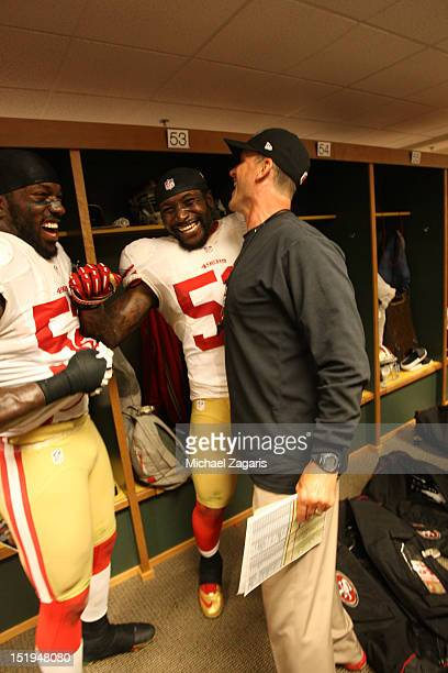 Head Coach Jim Harbaugh of the San Francisco 49ers celebrates with Patrick Willis and NaVorro Bowman in the locker room following the game against...
