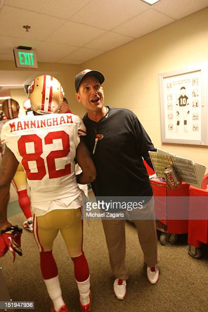 Head Coach Jim Harbaugh of the San Francisco 49ers greets Mario Manningham in the locker room following the game against the Green Bay Packers at...