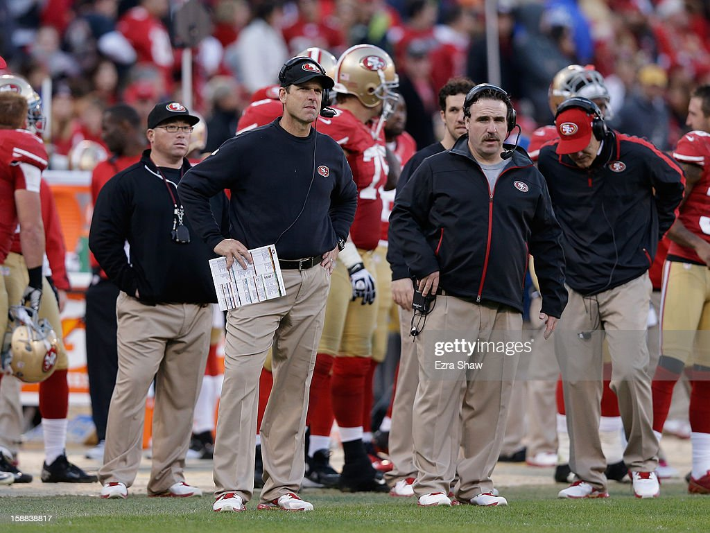 Head coach Jim Harbaugh of the San Francisco 49ers (left) stands next to defensive line coach Jim Tomsula the Arizona Cardinals at Candlestick Park on December 30, 2012 in San Francisco, California.
