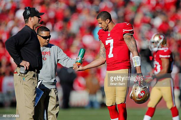 Head coach Jim Harbaugh of the San Francisco 49ers strategizes while quarterback Colin Kaepernick rinses his hands during a game against the Seattle...