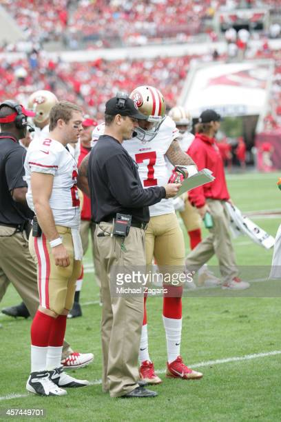 Head Coach Jim Harbaugh of the San Francisco 49ers talks with Colin Kaepernick and Colt McCoy during the game against the Tampa Bay Buccaneers at...