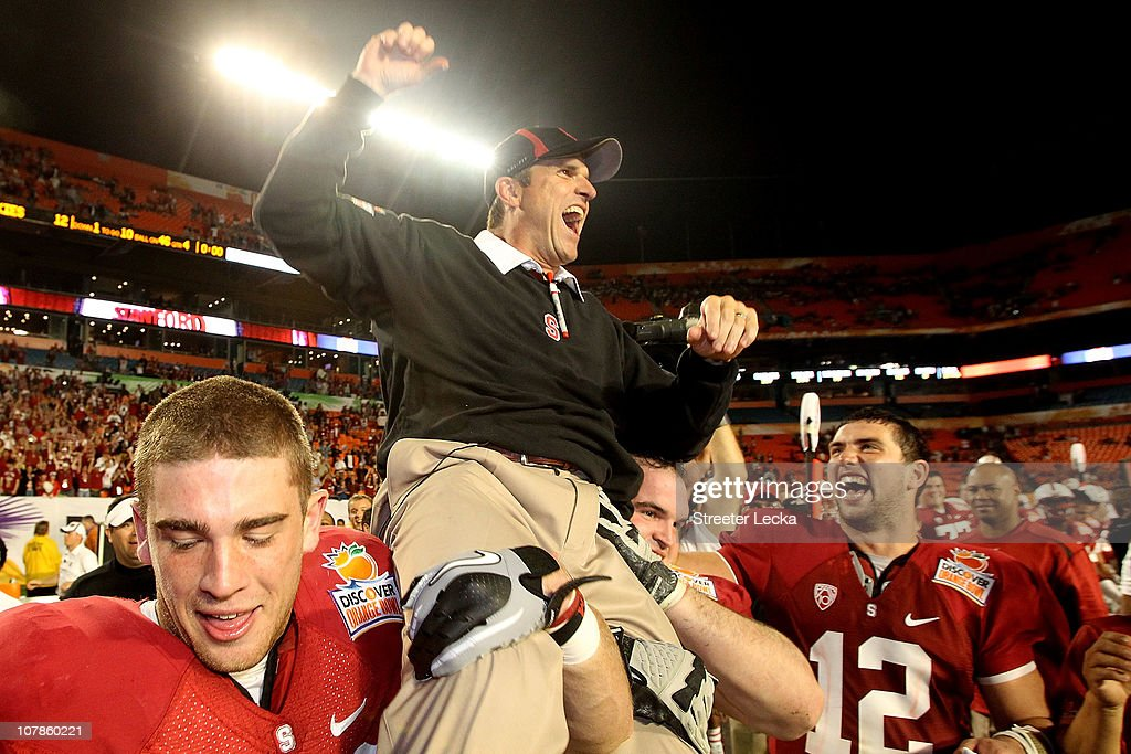 Head coach Jim Harbaugh of the Stanford Cardinal celebrates as he is lifted up by his players including Orange Bowl MVP Andrew Luck #12 (R) after Stanford won 40-12 against the Virginia Tech Hokies during the 2011 Discover Orange Bowl at Sun Life Stadium on January 3, 2011 in Miami, Florida.