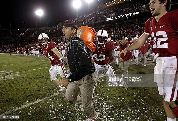 Head coach Jim Harbaugh of the Stanford Cardinal is covered with water from a Gatorade cooler by Andrew Luck and Chike Amajoyi after the Cardinal...