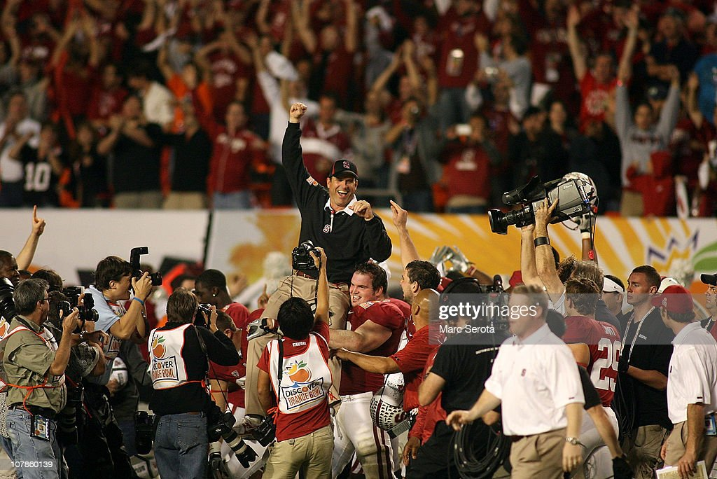 Head coach Jim Harbaugh of the Stanford Cardinal is lifted up by his players as they celebrate their 40-12 win against the Virginia Tech Hokies during the 2011 Discover Orange Bowl at Sun Life Stadium on January 3, 2011 in Miami, Florida.