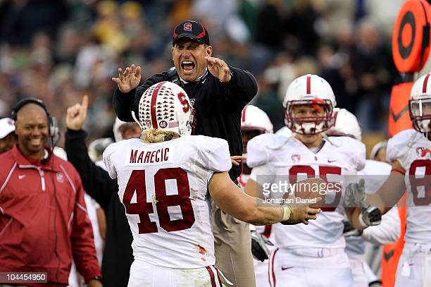 Head coach Jim Harbaugh of the Stanford Cardinal jumps to greet Owen Marecic after Marecic intercepted a pass for a touchdown against the Notre Dame...