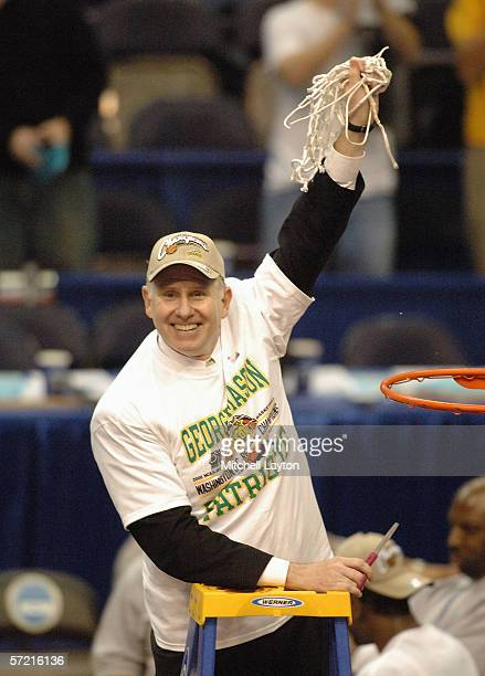 Head coach Jim Larranaga of the George Mason Patriots cuts down the nets following the game against the Connecticut Huskies in the Regional Finals of...