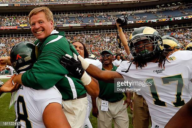 Head coach Jim McElwain of the Colorado State Rams celebrates with his team after defeating the Colorado Buffaloes 2217 in the Rocky Mountain...