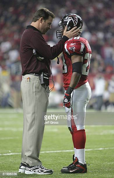 Head coach Jim Mora Jr of the Atlanta Falcons and Warrick Dunn talk during the fourth quarter the NFC Divisional Playoff game against the St Louis...