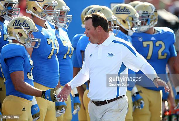 Head coach Jim Mora of the UCLA Bruins greets his players during warmups before the game against the Nebraska Cornhuskers at the Rose Bowl on...