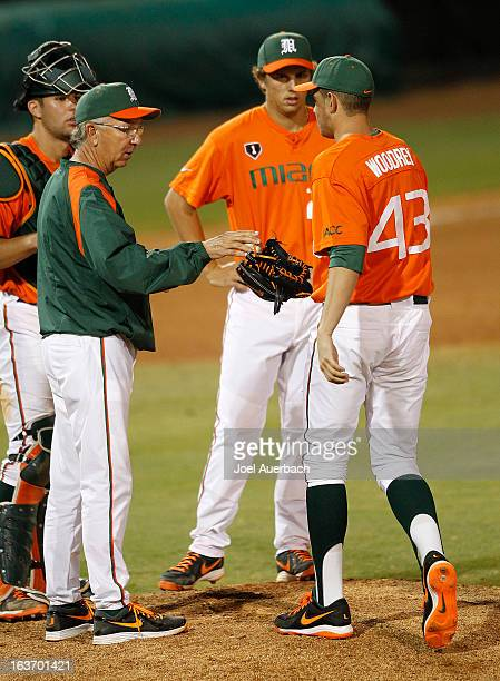 Head coach Jim Morris hands the ball to Thomas Woodrey of the Miami Hurricanes as he is brought in to pitch against the Illinois State Redbirds on...