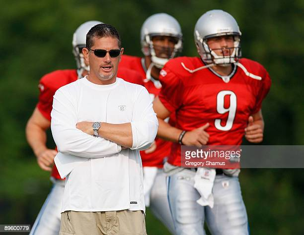 Head coach Jim Schwartz looks on while Matthew Stafford and Daunte Culpepper warm up during training camp at the Detroit Lions Headquarters and...