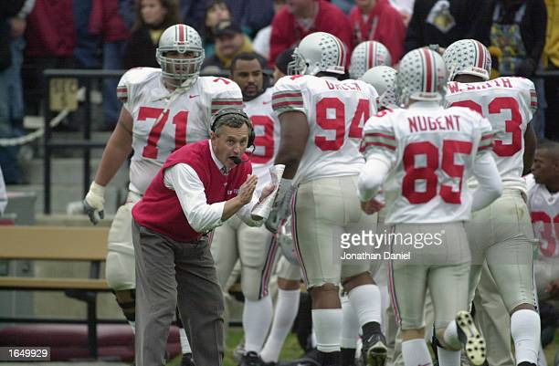 Head coach Jim Tressel of the Ohio State Buckeyes cheers on his players after taking the lead in the fourth quarter during the Big 10 Conference...