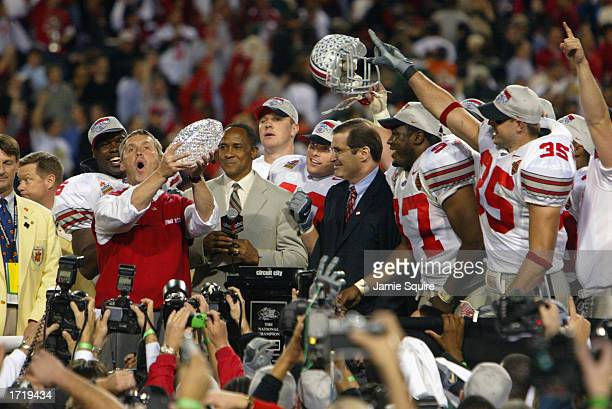 Head coach Jim Tressel of the Ohio State Buckeyes holds up the National Championship trophy after his team defeated the University of Miami...