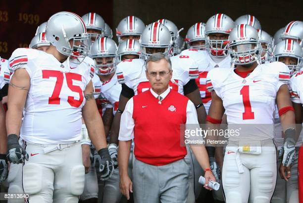 Head coach Jim Tressel of the Ohio State Buckeyes leads teammates Alex Boone and Marcus Freeman out onto the field before the college football game...