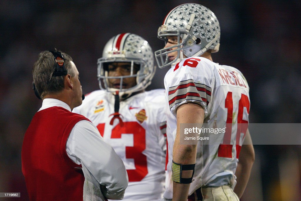 Head coach Jim Tressel of the Ohio State Buckeyes talks with running back Maurice Clarett #13 and quarterback Craig Krenzel #16 during the Tostitos Fiesta Bowl against the University of Miami Hurricanes at Sun Devil Stadium on January 3, 2003 in Tempe, Arizona. Ohio State won the game 31-24 in double-overtime, winning the NCAA National Championship.
