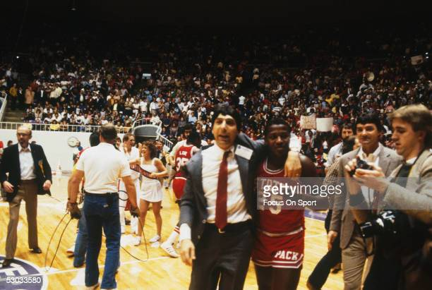 Head coach Jim Valvano of the North Carolina State Wolfpack walks off the court with a player afterwinning a game