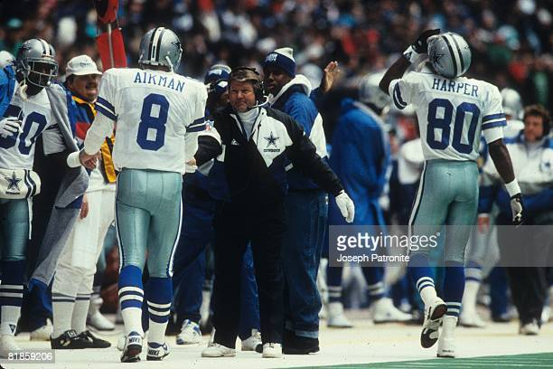 Head coach Jimmy Johnson of the Dallas Cowboys congratulates quarterback Troy Aikman on the sideline against the Philadelphia Eagles at Texas Stadium...