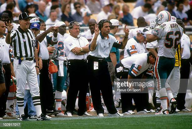 Head coach Jimmy Johnson of the Miami Dolphins in this portrait with his arms folded watching the action against the New England Patriots from the...