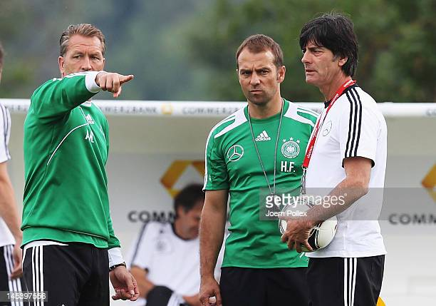 Head coach Joachim Loew and assistent coach HansDieter Flick and goalkeeper coach Andreas Koepke chat during a Germany training session at Stadium...