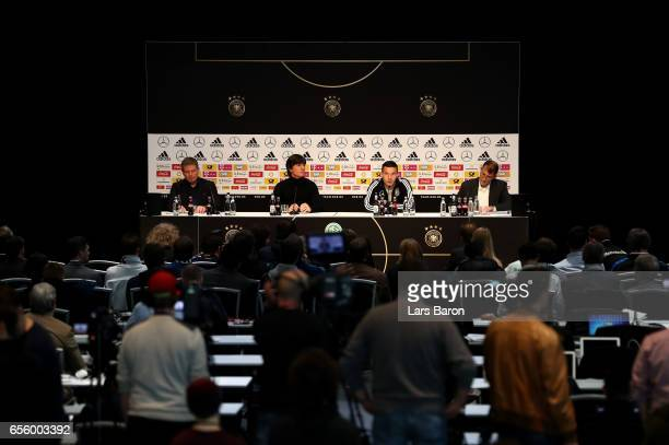 Head coach Joachim Loew looks on next to Lukas Podolski during a press conference of the German national team ahead of the international friendly...