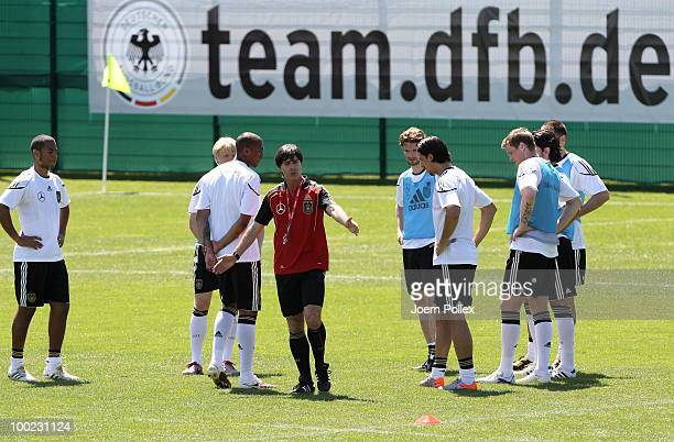 Head coach Joachim Loew of Germany and player of the German national team are seen during a training session at Sportzone Rungg on May 22, 2010 in...