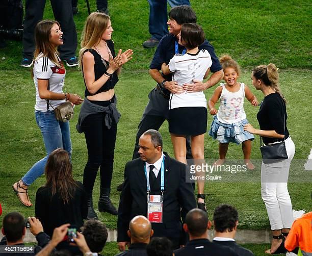 Head coach Joachim Loew of Germany hugs Kathrin Gilch girlfriend of Manuel Neuer of Germany as Montana Yorke girlfriend of Andre Schuerrle of Germany...