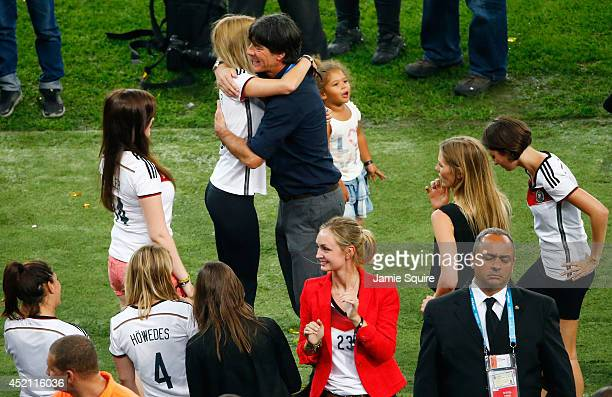 Head coach Joachim Loew of Germany hugs Lisa Weidenfeller wife of Roman Weidenfeller of Germany as Sarah Brandner girlfriend of Bastian...