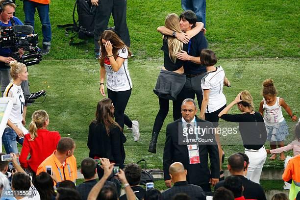 Head coach Joachim Loew of Germany hugs Sarah Brandner girlfriend of Bastian Schweinsteiger of Germany as Kathrin Gilch girlfriend of Manuel Neuer of...