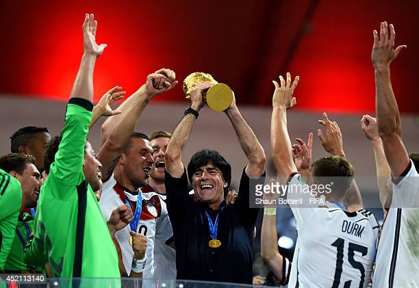 Head coach Joachim Loew of Germany lifts the World Cup to celebrate with his players during the award ceremony after the 2014 FIFA World Cup Brazil...
